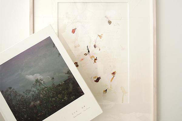 代官山のaoで展示された、紙の上にドライフラワーが散らされた作品の前で