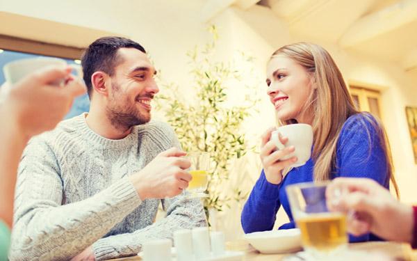 食卓で向かい合って会話をする男女