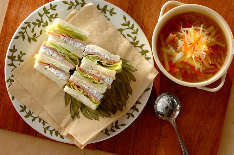 ペーパーの敷かれた皿に盛り付けられたハムのハーブサンドと野菜スープ